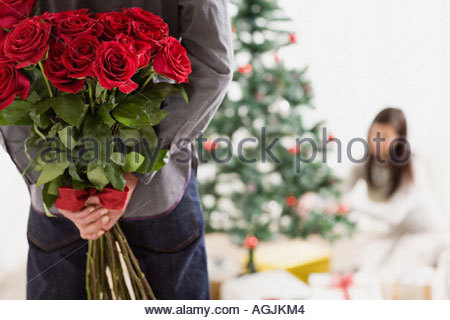man-holding-surprise-gift-of-roses-agjkm4